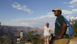 Grand Canyon National Park intern Mi-Kal White looks waits for visitors to approach him for assistance on July 26, 2016. As the National Park Service prepares to celebrate its 100th anniversary on Aug. 25, the agency is working to attract more minorities to the country's national parks and monuments as the demographics of America are expected to change dramatically in the coming years.