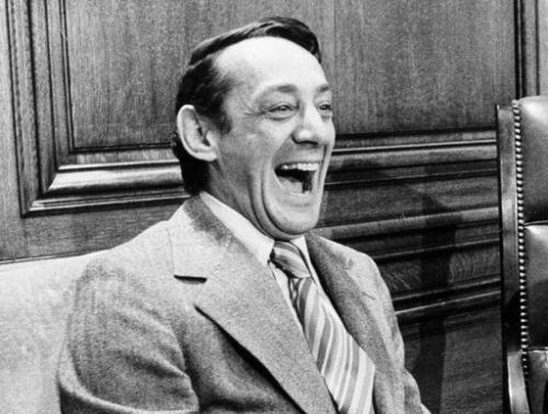 FILE - In this April 1977 file photo, San Francisco supervisor Harvey Milk sits in the mayor's office during the signing of the city's gay rights bill in San Francisco. The Navy is naming a ship in honor of the late gay rights leader, who served in the Navy for four years before he began a career in San Francisco city government. Navy Secretary Ray Mabus announced the decision to name the ship, which is one of a new fleet of replenishment oilers that will be built in San Diego.