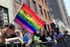 FILE - In this June 26, 2016, file photo, a woman holds a rainbow flag during the NYC Pride Parade in New York. Young Americans overwhelmingly say they support LGBT rights when it comes to employment, health care and adoption. That's according to a new GenForward survey, which finds 92 percent of young adults support HIV and AIDs prevention, 90 percent support equal employment, and 80 percent support LGBT adoption. Across ethnic groups, large majorities of Americans aged 18 to 30 favor training police on transgender issues, government support for LGBT youth organizations and insurance coverage for transgender health issues.