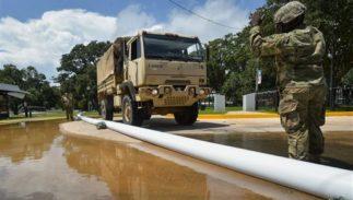 Members of the Louisiana Army National Guard help place sandbags to protect the city hall in Lake Arthur, La., Wednesday, Aug. 17, 2016.