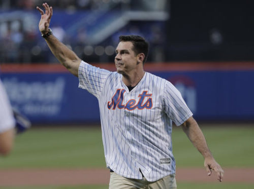 Former Major League Baseball player Billy Bean waves to baseball fans after throwing out the first pitch before the start of a baseball game between the New York Mets and the San Diego Padres, Saturday, Aug. 13, 2016, in New York. Bean threw out the pitch on the first Mets Pride Night.