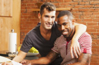Gay couple looking at paperwork in kitchen