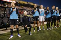 United States' Megan Rapinoe, second from left, kneels during the playing of the national anthem before the soccer match against Thailand, Thursday, Sept. 15, 2016 in Columbus, Ohio.  Rapinoe did not start the game against Thailand at Mapfre stadium. She knelt from a spot near the bench while the fellow reserves around her stood.