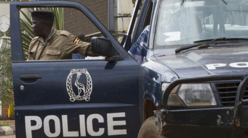 A Ugandan police officer stands outside of his vehicle.