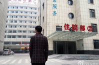 Yu Hu stands in front of Zhumadian Psychiatric Hospital.