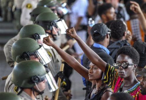 """Ebonay Lee, center, and another unidentified woman holds up their fists in front of a line of police and protesters, Wednesday, Sept. 28, 2016, in El Cajon, Calif. Dozens of demonstrators on Wednesday protested the killing of a black man shot by an officer after authorities said the man pulled an object from a pocket, pointed it and assumed a """"shooting stance."""""""
