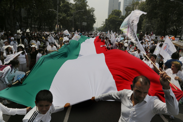 Demonstrators walk with a giant Mexican national flag during a march organized by representatives of the National Front for the Family, in Mexico City, Saturday, Sept. 24, 2016.