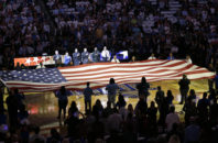 First responders hold a flag on the court as the national anthem is played during a tribute to the victims of the Pulse nightclub shooting prior to an NBA basketball game between the Orlando Magic and the Miami Heat, Wednesday, Oct. 26, 2016, in Orlando, Fla.