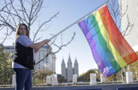 "FILE - In this Nov. 14, 2015, file photo, Sandy Newcomb poses for a photograph with a rainbow flag as Mormons gather for a mass resignation from the Church of Jesus Christ of Latter-day Saints, in Salt Lake City. Mormon leaders are telling gay and lesbian church members that attraction to people of the same sex is not a sin or a measure of their faithfulness. But they are reminding those members that acting on those feelings by having sex violates fundamental doctrinal beliefs that won't change. The message is part of the Mormon church's ""Mormon and Gay"" website launched Tuesday, Oct. 25, 2016, with dozens of articles, teachings, videos and stories from Mormons who identify themselves as gay."