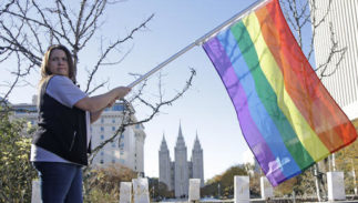 """FILE - In this Nov. 14, 2015, file photo, Sandy Newcomb poses for a photograph with a rainbow flag as Mormons gather for a mass resignation from the Church of Jesus Christ of Latter-day Saints, in Salt Lake City. Mormon leaders are telling gay and lesbian church members that attraction to people of the same sex is not a sin or a measure of their faithfulness. But they are reminding those members that acting on those feelings by having sex violates fundamental doctrinal beliefs that won't change. The message is part of the Mormon church's """"Mormon and Gay"""" website launched Tuesday, Oct. 25, 2016, with dozens of articles, teachings, videos and stories from Mormons who identify themselves as gay."""