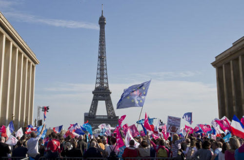 Demonstrators wave flags at Trocadero plaza to protest gay marriage in Paris, Sunday, Oct. 16, 2016. Thousands of people have marched in Paris to call for the repeal of a law allowing gay marriage, six months before France's next presidential election. Eiffel tower in the background.