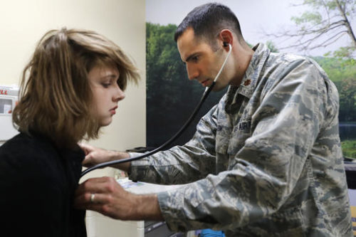 In this Sept. 7, 2016, photo, Dr. David Klein, chief of adolescent medicine at Fort Belvoir Community Hospital and an Air Force Major, listens to the heartbeat of Jenn Brewer, 13, at her monthly doctors appointment visit for monitoring of her treatment at the Pediatric Clinic at Fort Belvoir Community Hospital in Fort Belvoir, Va. Brewer is transitioning from male to female. Starting Oct. 3, the military's health insurance will cover transgender-related services that include hormone therapy and supportive counseling.