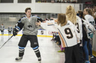 In this photo provided by the NWHL, date not known, Buffalo Beauts forward Harrison Browne high-fives fans during player introductions before a game in Buffalo, N.Y. Browne is preparing to make his debut for the National Women's Hockey League Buffalo Beauts as the second-year professional league's first transgender player.