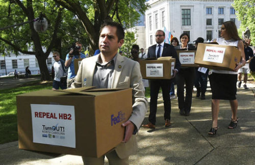 """FILE - In this April 25, 2016, file photo, State Rep. Chris Sgro, D-Guilford, who is also executive director of Equality NC, leads a group carrying petitions calling for the repeal of House Bill 2 to Gov. Pat McCrory's office at the state Capitol building in Raleigh, N.C. As North Carolina has a bit of an identity crisis, its election for governor and even president will be a referendum on the state's right turn and contentious new laws. """"North Carolina IS a progressive state,"""" insists Sgro. """"What really happened is that in a low-turnout year, Democrats lost in 2010, and Republicans slammed our state with the worst possible redistricting that turned everywhere in the state into unwinnable conservative districts."""""""