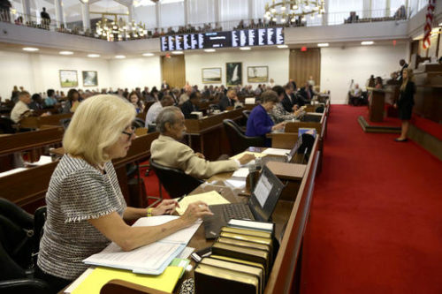 FILE- In this June 23, 2016, file photo, Rep. Becky Carney, D-Mecklenburg, foreground, and other North Carolina lawmakers gather for a House session at the General Assembly in Raleigh, N.C. Republicans control both the Senate and the House and are expected to retain their majorities following the November elections. Democrats, however, are seeking to flip enough seats to end the GOP's veto-proof majorities in one or both chambers.