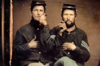 Unidentified soldiers in Union uniforms holding cigars in each other's mouths, ca. 1860s
