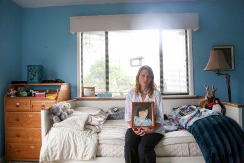 Katharine Prescott holds a framed photo of her transgender son, Kyler.