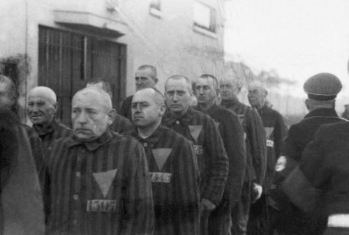 Prisoners wearing the pink triangle at the concentration camp at Sachsenhausen, Germany, are marched outdoors by Nazi guards on December 19, 1938.