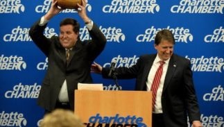John McCabe, left, senior vice-president of Global Operations at PayPal, holds up a carved wooden bowl (made by an artist from a tree struck by lightning outside the state capitol), presented to him by Gov. Pat McCrory, right, after McCrory announced that PayPal, Inc. will open a Global Operations Center in Charlotte. PayPal canceled its plans for the expansion soon after House Bill 2 was passed.