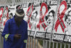 FILE -- In this Dec. 1, 2014 file photo a man makes a call on a mobile phone as he passes World AIDS Day banners on the perimeter of an office building in Sandton, Johannesburg, South Africa.  A new vaccine against HIV, called HVTN 702, is to be tested in South Africa, it is announced Sunday Nov. 27, 2016, and scientists aims to enroll 5,400 sexually active men and women for the clinical trial.