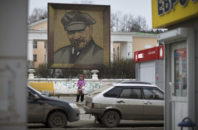 In this Thursday, Oct. 27, 2016 photo, a woman waits for a bus at a bus stop in front of a huge portrait of the Soviet Union leader Joseph Stalin in the central square of a small town just outside Yekaterinburg, Russia.
