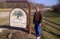 Owner Jim Walder stands beside the sign for Timber Creek Bed and Breakfast in central Illinois.