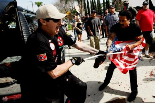 A Ku Klux Klansman, left, fights a counter protester for an American flag after members of the KKK tried to start a