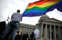 Protesters wave flags on March 24 outside the North Carolina Executive Mansion in Raleigh, N.C. North Carolina passed a law that bans cities and counties from passing anti-discrimination ordinances.