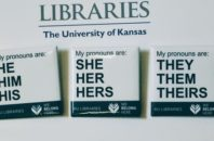 """In this Tuesday, Dec. 27, 2016 photo, buttons advertising part of the University of Kansas Libraries' """"You Belong Here"""" campaign are displayed in Lawrence, Kansas. The campaign is aimed at making undergraduates, including those who are transgender, feel welcome. A number of University of Kansas Libraries employees now wear the buttons showing their gender pronouns."""