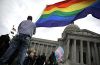 """FILE - In this March 31, 2016, file photo, gay-rights supporter Mathew """"Skippy"""" Mauldin holds a flag during a gay rights rally outside the Capitol in Jefferson City, Mo. A Republican Missouri lawmaker says he has a solution to end tense debates over same-sex marriage. Rep. T.J. Berry wants to take government out of marriage and leave it to houses of worship by classifying such legal partnerships as domestic unions."""