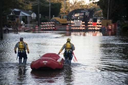 A swift water rescue team down a street covered by floodwaters caused by rain from Hurricane Matthew in Lumberton, N.C.