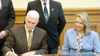 In this 2014 photo, Indiana Rep. Cindy Kirchhofer watches on as then-Gov. Mike Pence signs a bill she authored into law.