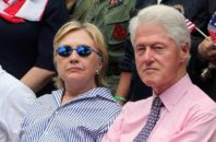 Democratic presidential candidate Hillary Clinton sits with her husband, former President Bill Clinton, as they attend a ceremony after walking in a Memorial Day parade.