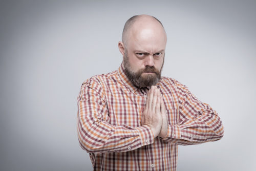 Angry man staring at camera with hands folded in prayer
