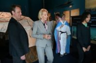 Betsy DeVos tours a school while Torin Hodgman wears a trans flag in the background.