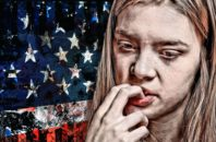 A young white woman bites her nails in front of a ragged and dark American flag