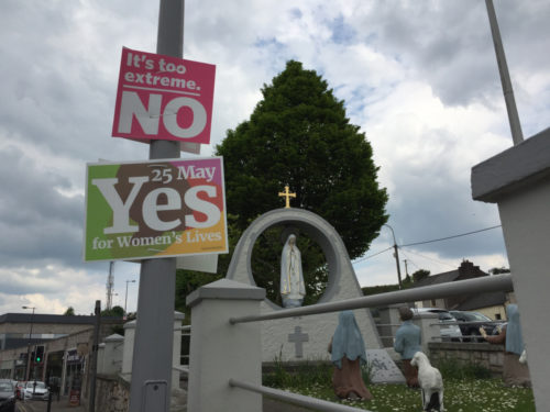 "Two signs hang on a lamppost before a Christian statue. One says ""Vote Yes."" The other ""Vote No."""