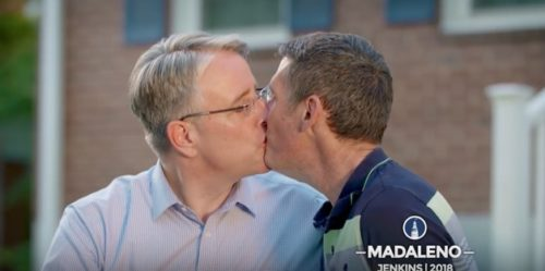 Richard Madaleno kisses his husband, Mark Hodge, in front of their home.