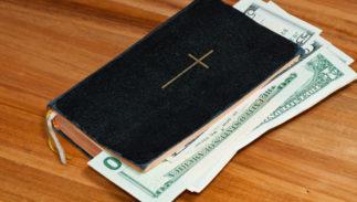 A Christian Bible stuffed with dolllars