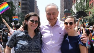 NY Senator Chuck Schumer embraces his daughter and her fiancee at the NYC Pride Parade.