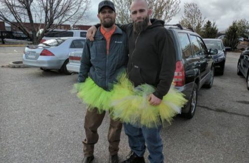 Two men wearing bright tutus overtop of regular clothes