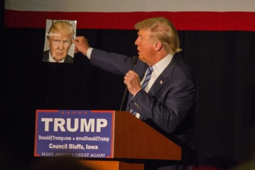 Presidential candidate Donald Trump holds up a magazine cover featuring himself while at a campaign stop at the Mid-America Center in Council Bluffs, Iowa.