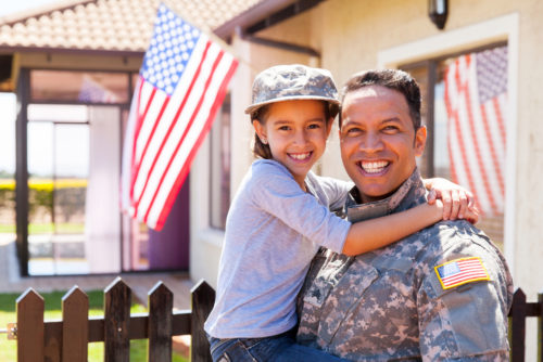 A Latino US Army soldier holds his daughter in front of his home