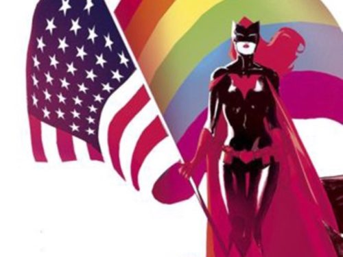 Batwoman stands in front of the American and rainbow flags.