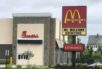 """A McDonalds sign reading """"We Welcome Everyone"""" with the soon-to-open Chick-fil-A behind it."""