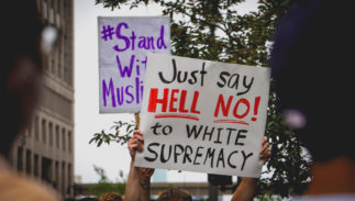 "JUNE 26, 2018: Protestors hold signs that say ""Just say hell no to white supremacy"" to protest the supreme court's ruling on the muslim ban in Detroit, MI."