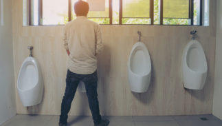 A man stands at a bank of urinals