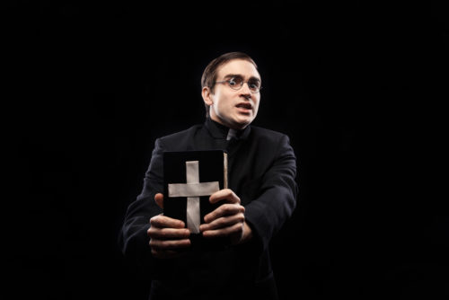 Portrait of frightened young catholic priest against black background