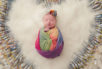 Photo of London O'Neill, wrapped in rainbow-color swaddling and surrounded by IVF needles