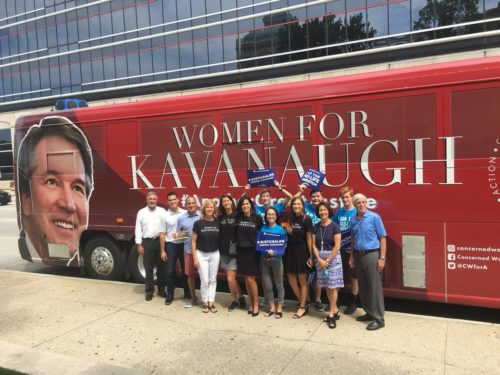 """Photo of six women and seven men standing in front of a """"Women for Kavanaugh"""" sign"""
